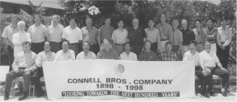 """Group of Connell employees with a banner, Connell Bros. Company 1898-1998. """"Looking towards the next hundred years."""